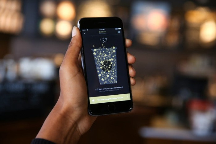 A person holding a phone with the Starbucks app loaded.