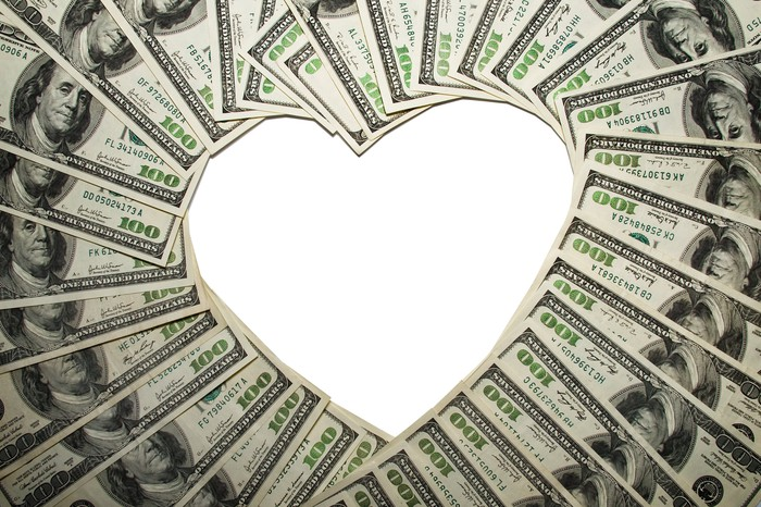 Hundred dollar bills fanned out to form a heart shape in their center.
