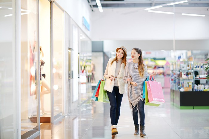 Two smiling women walking while carrying shopping bags at a mall.