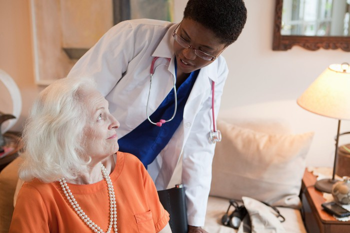 A woman with a white coat and stethoscope checks in on an elderly patient.