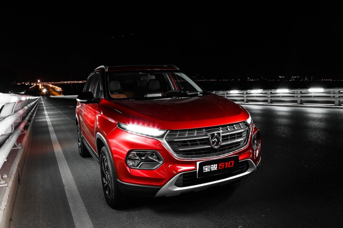 A red Baojun 510 SUV on a bridge, at night.