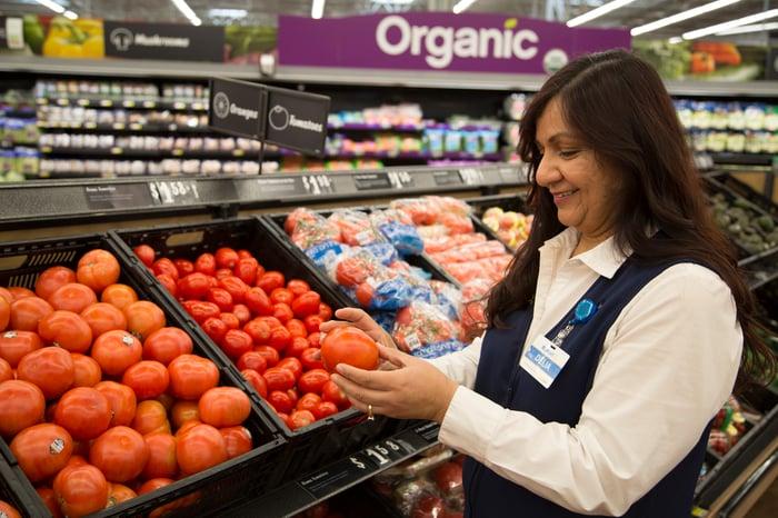 A Walmart employee examining a tomato.
