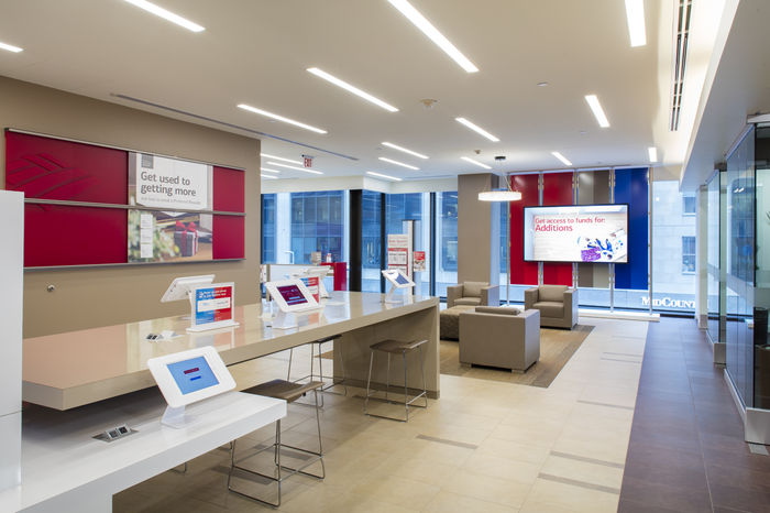 Lobby of a modern Bank of America branch, with white counters and tablets on top and comfy beige chairs in the background.
