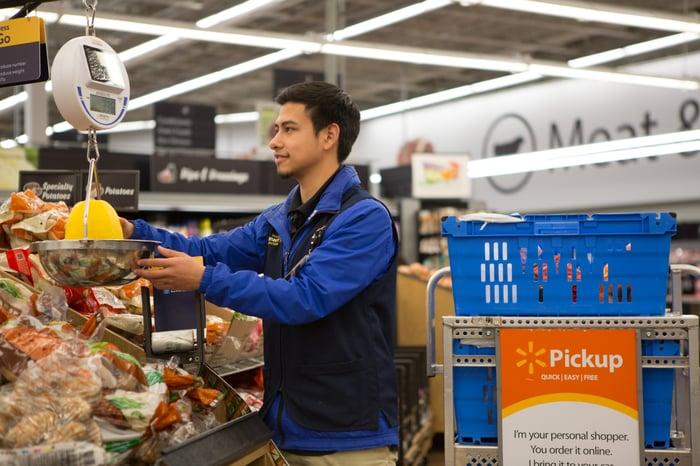 A Walmart associate weighing produce.