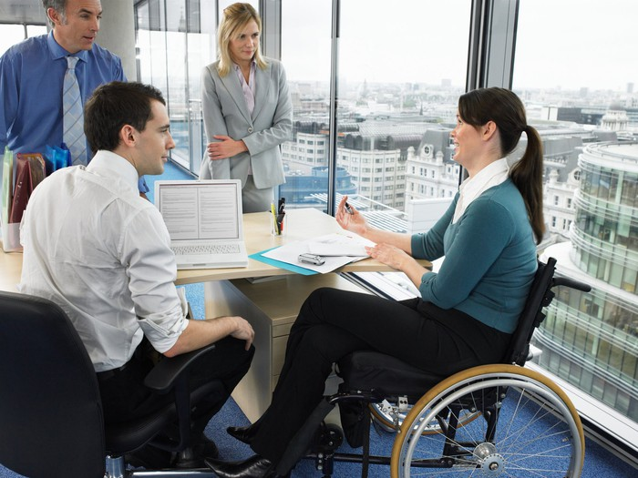 A woman and a man standing, a man sitting, and a woman in a wheelchair converse around a table.
