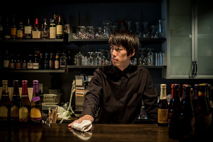 Young bartender in a contemporary Japanese bar.