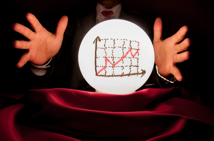 Man in suit and tie holding hands around a crystal ball with a stock chart indicating gains