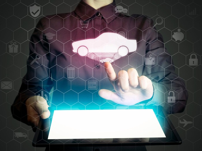 A man holding a tablet computer. Above the tablet, a simple image of a car floats in the air amid various icons related to money, shopping, and communications. He is clicking on the car image..