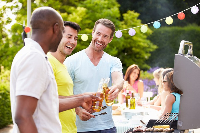 Men drinking beer outdoors while cooking on a grill.