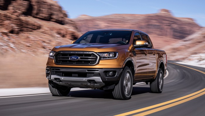 A bronze-colored Ford Ranger, a midsize pickup truck, on a mountain road