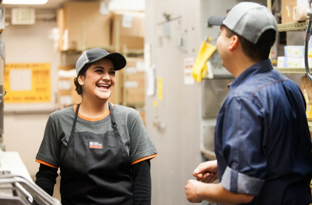 A Taco Bell workers talks to another Taco Bell worker.