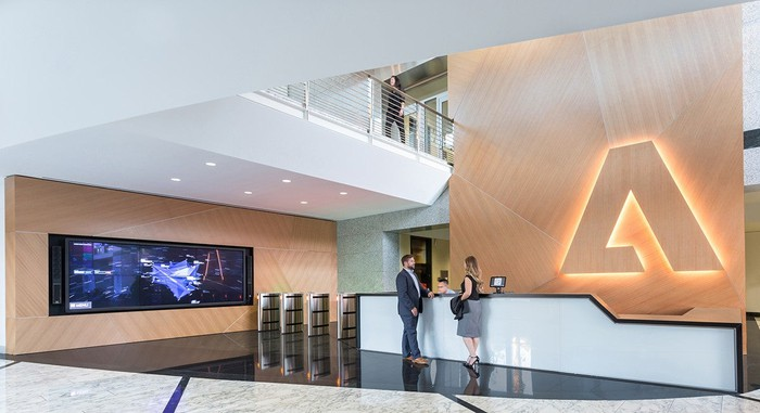 Adobe headquarters office front desk with three employees talking and the glowing Adobe logo in the background