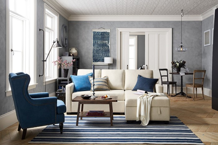 Furnished room with a blue armchair, tan couch, and blue-and-tan rug.