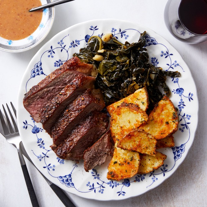 A Blue Apron meal on a white and blue dish featuring beef, potatoes, and kale.