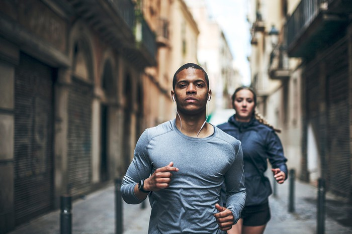 A man and a woman jogging while listening to music