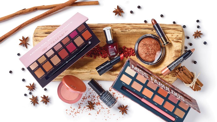 Several different cosmetic products on a white background and wood plank.