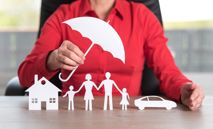 Woman in red shirt holding a paper umbrella over paper cutouts of a family, a house, and a car.