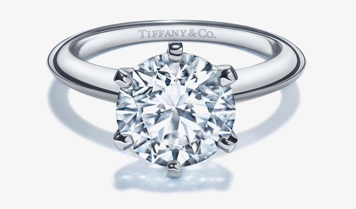 Large diamond, silver-colored engagement ring with Tiffany & Co. printed inside the band.