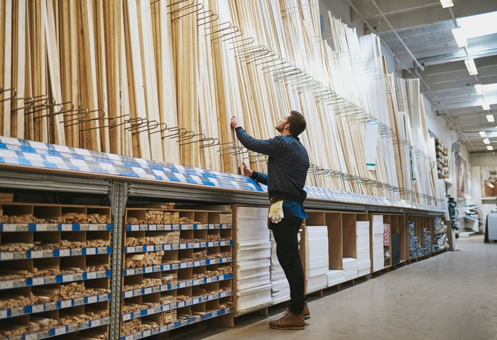 A man looks at wooden planks inside a home improvement warehouse.