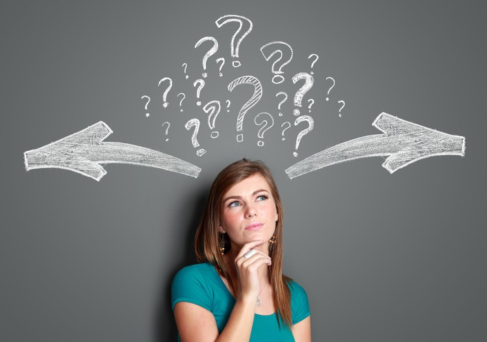 A woman with a ponderous expression stands with her back to a chalkboard, on which is drawn a series of question marks and arrows pointing in opposite directions.