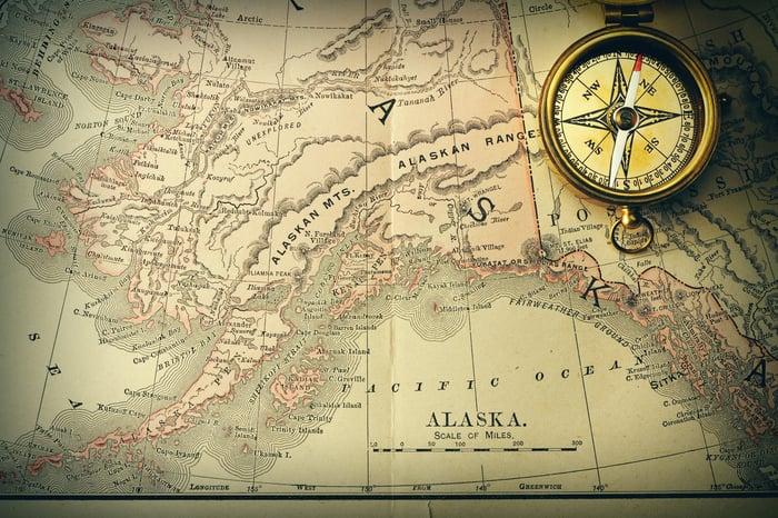 An antique compass sits on a nineteenth-century map of Alaska.