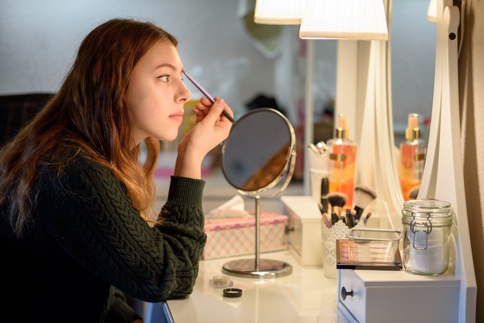 Young woman applies eyeshadow in a mirror viewed in profile.