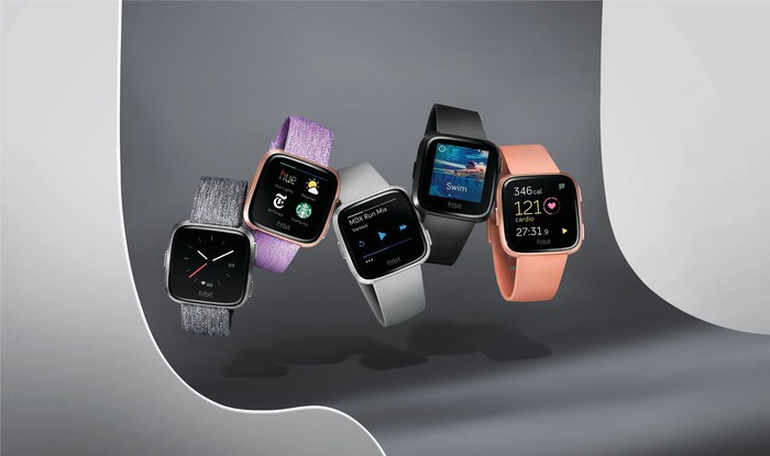 An assortment of Fitbit Versa smartwatches in different colors