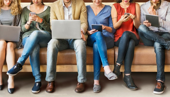 Young people sit in a row using a variety of devices.