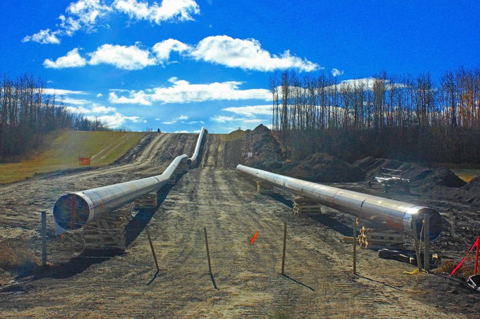 A pipeline under construction with a blue sky up ahead.