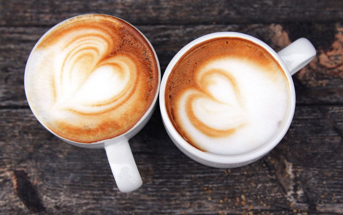 Two coffee cups topped with milk froth on a wooden table