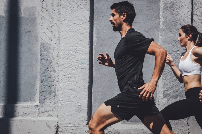 A man and woman running while wearing Lululemon apparel.
