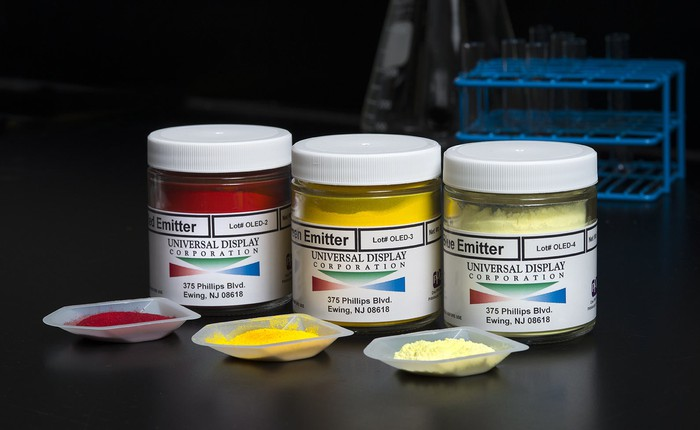 Three labeled containers -- in red, dark yellow, and light yellow -- with OLED emitter materials made by Universal Display.