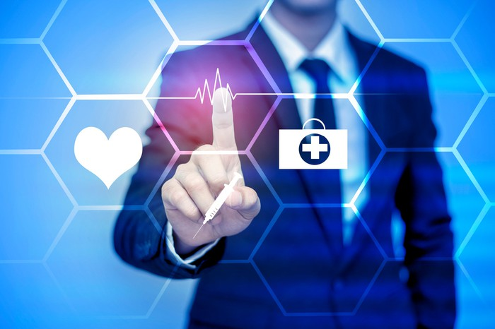 Businessman pointing to healthcare icons on virtual screen