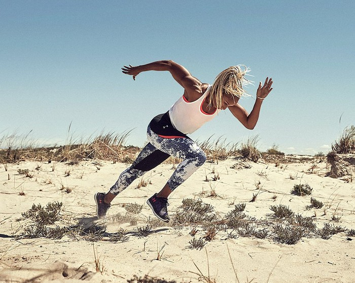 Under Armour athlete Natasha Hastings sprinting in sand with a blue sky in the background.