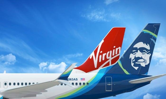 A Virgin America airplane tail behind an Alaska Airlines plane
