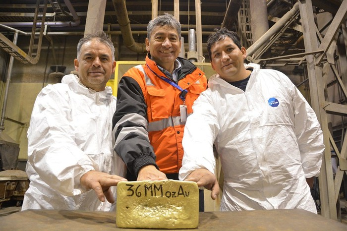 Three people standing behind a huge bar of gold.