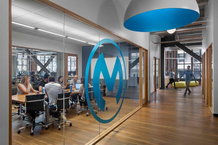 Hallway and glass-walled conference room with large blue M logo on the window.