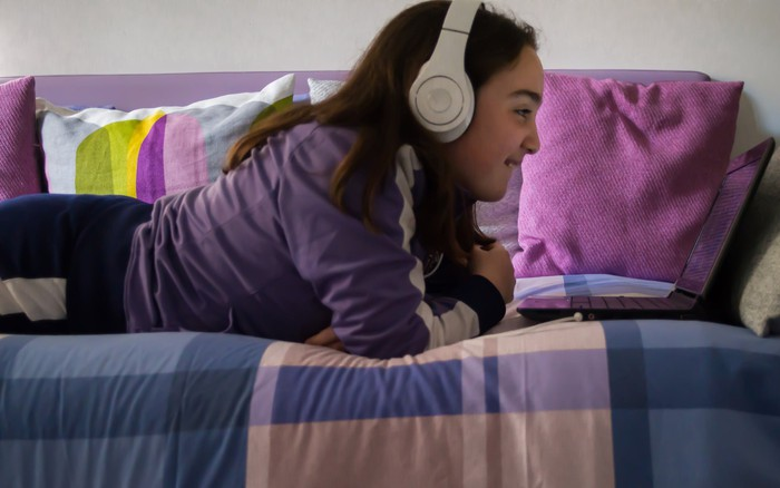 A young girl laying on a daybed wearing headphones, smiling and looking at a laptop.