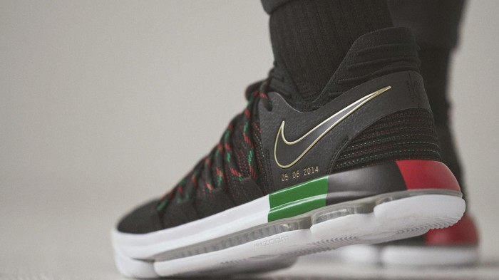 Black, red, green, and white Nike Durant Equality Sneaker on someone's feet.