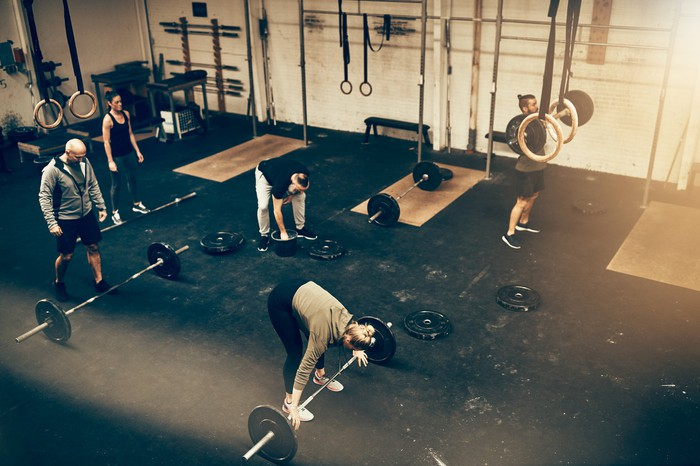 High angle of a group of fit people working out together during a weightlifting class at a gym.