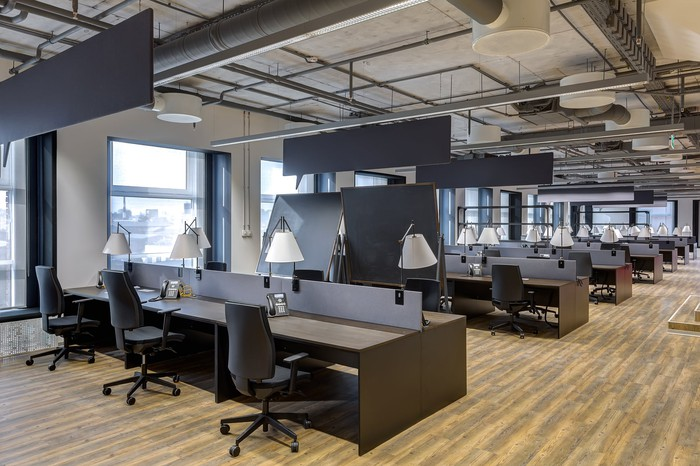 Rows of workspaces in a modern, open office.
