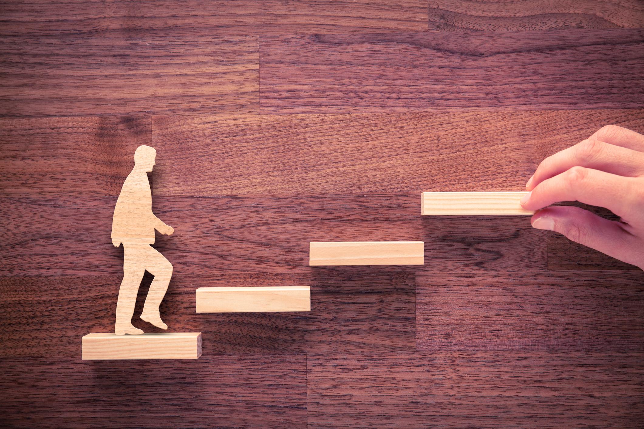 A wooden man walks up a set of steps.