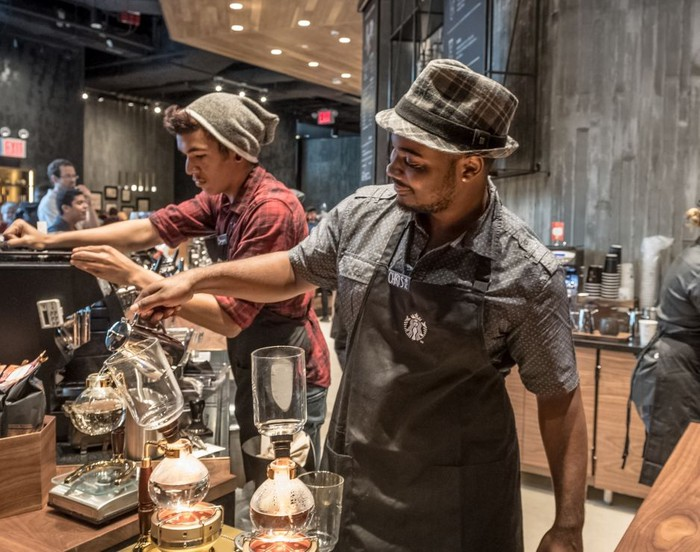 Two male Starbucks baristas prepare beverages at its Reserve roastery.