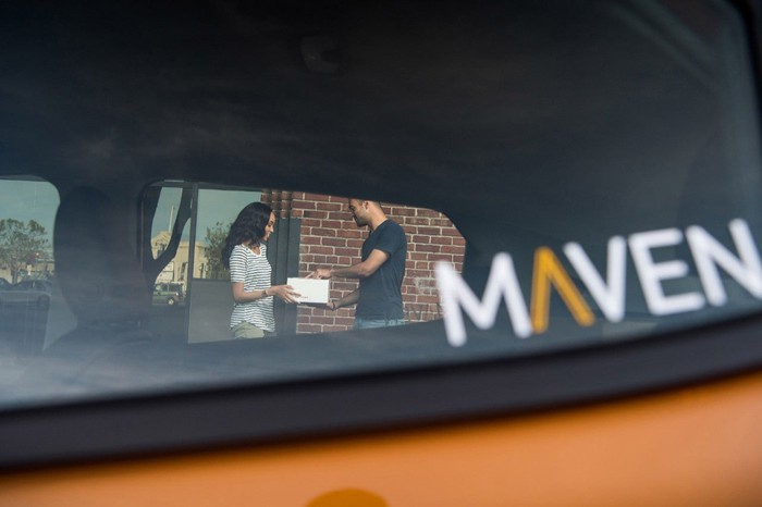 Consumers in the background seen through windshield of Maven car.