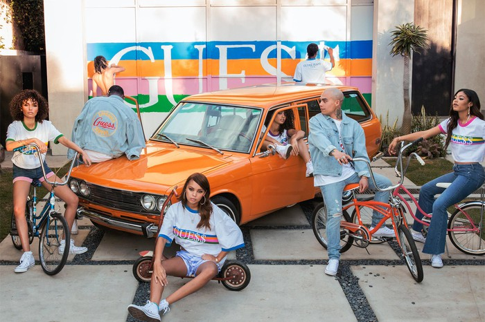 Six fashion models sitting on bicycles in front of an orange car with the Guess logo painted on a building wall.