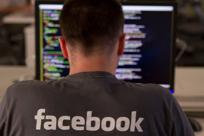 An engineer in a Facebook company shirt, with his back turned, writing code on his computer.