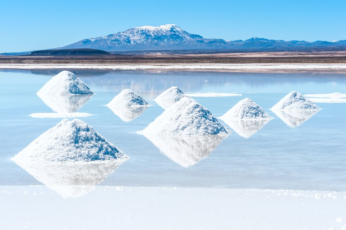 A lithium salt flat -- showing an evaporation pond with mountains and a blue sky in background.