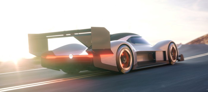 The VW I.D. R Pikes Peak, a low-slung grey racecar with a big rear wing, is shown on a mountain road.