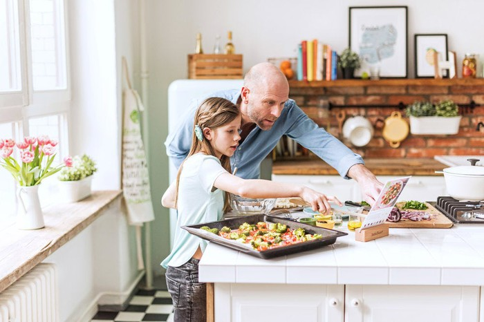 A man and young girl preparing a HelloFresh meal kit