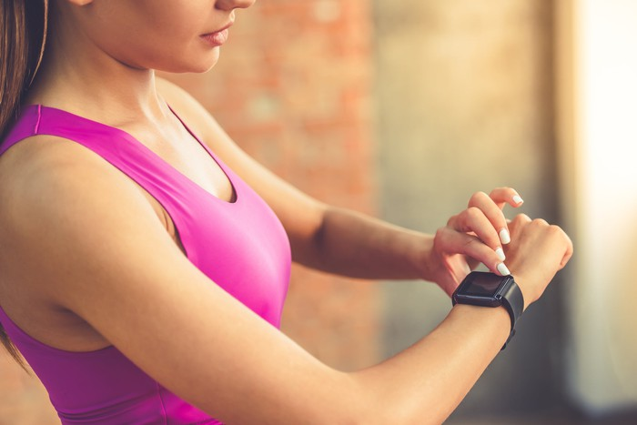 Woman in fitness clothing looking at a smartwatch